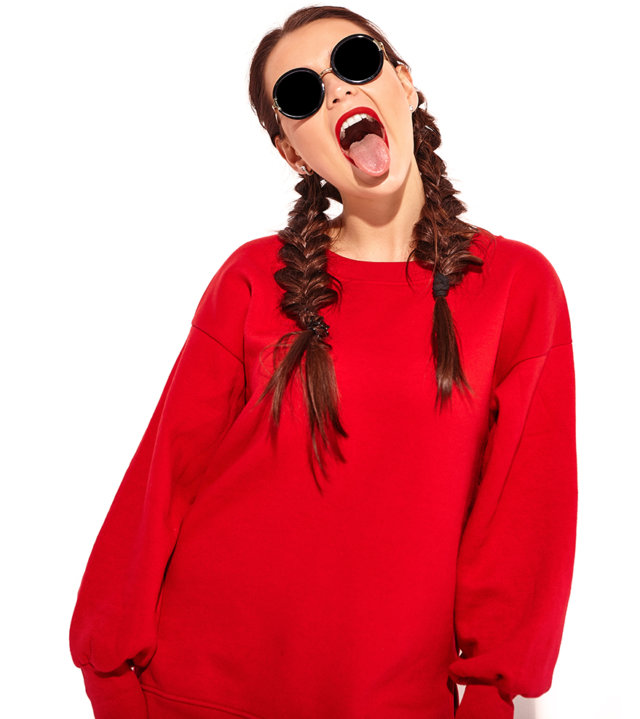 young happy smiling woman model with bright makeup and colorful lips with two horns and sunglasses in summer red clothes isolated on white. Going crazy and showing her tongue